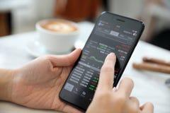 Vrouwelijke hand met smartphone handelvoorraad online in koffiewinkel, Bedrijfsconcept royalty-vrije stock foto's
