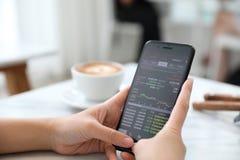 Vrouwelijke hand met smartphone handelvoorraad online in koffiewinkel, Bedrijfsconcept royalty-vrije stock afbeeldingen