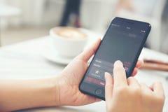 Vrouwelijke hand met smartphone handelvoorraad online in koffiewinkel, Bedrijfsconcept stock foto