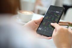 Vrouwelijke hand met smartphone handelvoorraad online in koffiewinkel, Bedrijfsconcept stock afbeelding