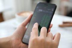 Vrouwelijke hand met smartphone handelvoorraad online in koffiewinkel, Bedrijfsconcept stock foto's