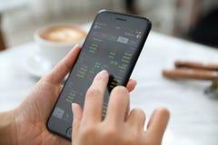 Vrouwelijke hand met smartphone handelvoorraad online in koffiewinkel, Bedrijfsconcept royalty-vrije stock foto