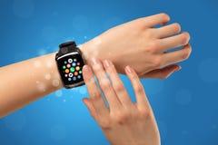Vrouwelijke hand met smartwatch en app pictogrammen Stock Foto's