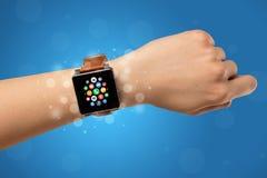 Vrouwelijke hand met smartwatch en app pictogrammen Stock Afbeeldingen