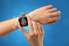 Vrouwelijke hand met smartwatch en app pictogrammen Royalty-vrije Stock Afbeeldingen