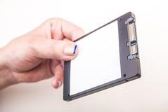 Vrouwelijke hand met SSD-aandrijving op wit Royalty-vrije Stock Foto's