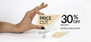 Vrouwelijke hand met zwarte spijkers, houdend schaar en knipsel een prijskaartje Stock Foto's