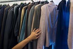 Vrouwelijke hand op mannelijke jasjes op rek Stock Foto