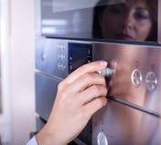 Vrouwelijke hand op ovenknoppen Stock Afbeeldingen