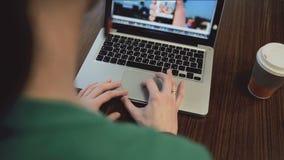 Vrouwelijke handen die aan laptop in koffie werken stock footage