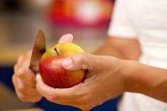Vrouwelijke handen die appel met mes snijden Stock Afbeeldingen