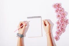 Vrouwelijke Handen die in Blocnote schrijven Stock Afbeeldingen