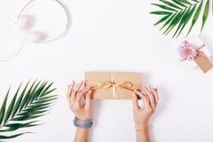 Vrouwelijke handen die boog op giftdoos binden Stock Afbeeldingen