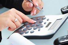 Vrouwelijke handen die calculator gebruiken royalty-vrije stock foto's