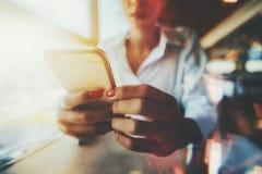 Vrouwelijke handen die cellphone in een restaurant houden royalty-vrije stock foto's