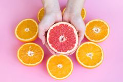 Vrouwelijke handen die de helft van een sappige rijpe rode die grapefruit boven sinaasappelen houden in de helft op een roze acht royalty-vrije stock foto