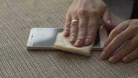 Vrouwelijke handen die de mobiele telefoon van het oppervlaktescherm met dicht omhoog doek afvegen stock video