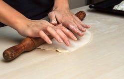 Vrouwelijke handen die deeg met deegrol voorbereiden stock afbeeldingen