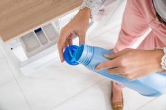 Vrouwelijke Handen die Detergens in Kroonkurk gieten Royalty-vrije Stock Afbeeldingen