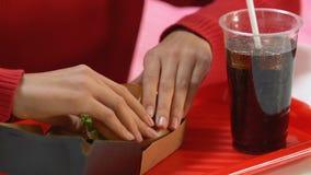 Vrouwelijke handen die doos met snel voedselhamburger openen, die ongezonde sandwich proeven stock footage