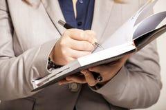 Vrouwelijke handen die een agend houden en een nota over het document schrijven Royalty-vrije Stock Foto's
