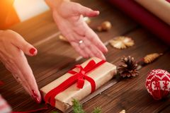 Vrouwelijke handen die een boog met rood die lint op giftbox binden, in ambachtdocument wordt verpakt stock foto's