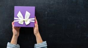 Vrouwelijke handen die een doos in de vorm van hart met een heden houden Stock Fotografie