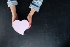 Vrouwelijke handen die een doos in de vorm van hart met een heden houden Stock Afbeeldingen