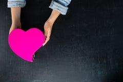 Vrouwelijke handen die een doos in de vorm van hart met een heden houden Royalty-vrije Stock Foto