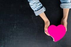 Vrouwelijke handen die een doos in de vorm van hart met een heden houden Royalty-vrije Stock Foto's