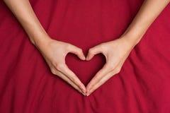 Vrouwelijke handen die een hart rode achtergrond 1 gestalte geven Royalty-vrije Stock Foto