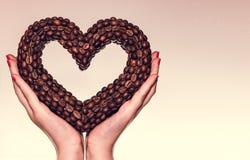 Vrouwelijke handen die een hart van de koffiebonen houden De dag van de valentijnskaart royalty-vrije stock foto's