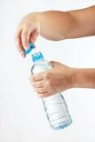 Vrouwelijke handen die een kleine fles zoet water openen royalty-vrije stock foto