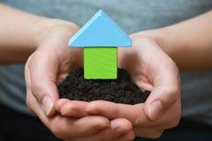 Vrouwelijke handen die een lap grond met blokhuis houden Ecologisch huis, bouw en onroerende goederenconcept Royalty-vrije Stock Afbeelding