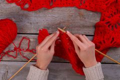 Vrouwelijke handen die een sjaal breien stock afbeeldingen