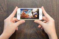 Vrouwelijke handen die een witte iPhone met Conflict van clans op s houden Royalty-vrije Stock Foto