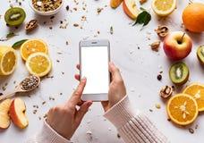 Vrouwelijke handen die gebruikend smartphone op gezonde voedselachtergrond houden royalty-vrije stock fotografie