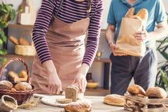 Vrouwelijke handen die geheel tarwebrood snijden Royalty-vrije Stock Afbeelding