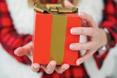 Vrouwelijke handen die giftdoos met rood lint houden Toevallige Stijl Stock Afbeelding