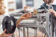 Vrouwelijke handen die gloeidraad houden die met extruder van 3D printer wordt verbonden stock afbeeldingen