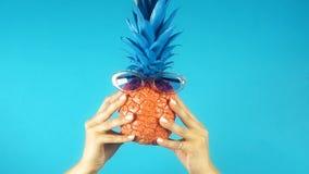 Vrouwelijke handen die grappige gekleurde ananas met zonnebril, tijd voor vakantie houden stock footage