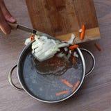 Vrouwelijke handen die groenteningrediënten zetten in kippensoep stock fotografie