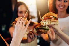 Vrouwelijke handen die grote smakelijke sappige hamburgers met vage vrouwen op achtergrond houden royalty-vrije stock afbeelding