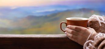 Vrouwelijke handen die hete kop van koffie of thee op de bergenachtergrond houden stock foto's