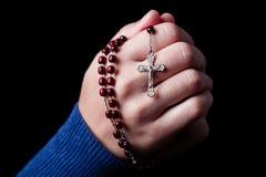 Vrouwelijke handen die houdend een rozentuin met Jesus Christ in het kruis of Kruisbeeld op zwarte achtergrond bidden royalty-vrije stock fotografie