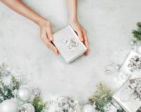 Vrouwelijke handen die huidige doos houden Giften, sparrentak en snuisterijenornamenten op grijze steenlijst Feestelijke achtergr royalty-vrije stock foto's