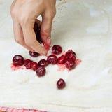 Vrouwelijke handen die kleine pastei met kers maken Stock Foto's