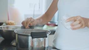Vrouwelijke handen die kokende soep zouten door lepel bij binnenlandse keuken, close-up stock video