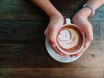 Vrouwelijke handen die kop van chocolade op houten achtergrond houden de bovenkant wedijvert Stock Foto's