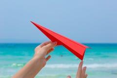 Vrouwelijke handen die met document vliegtuig op het strand spelen stock afbeelding